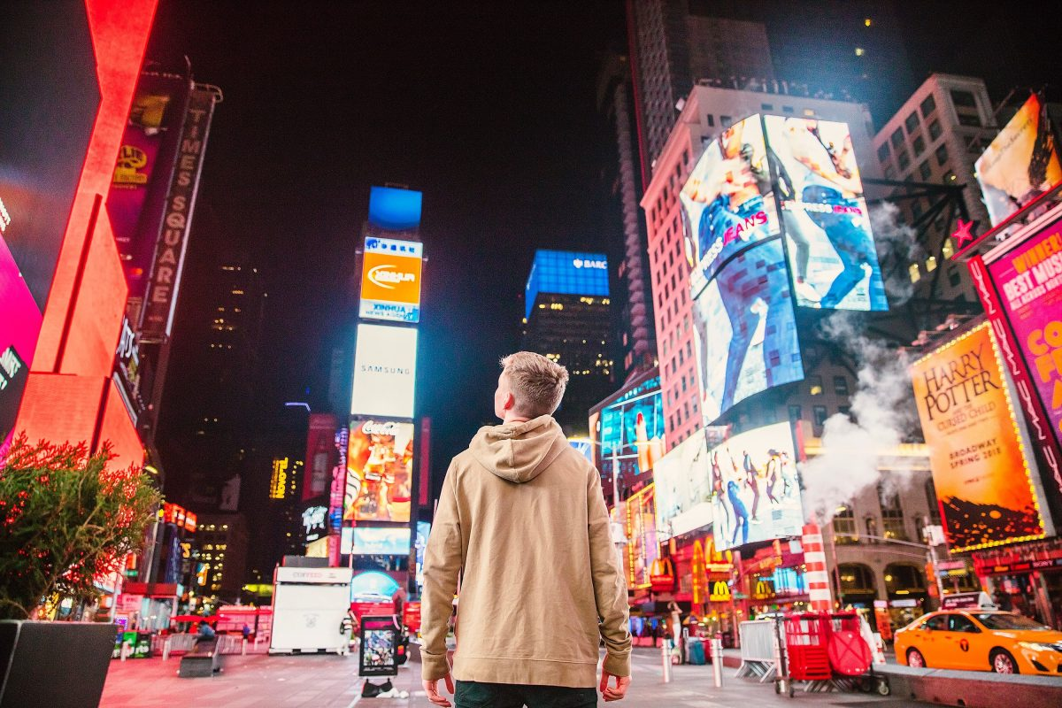 Man standing in front of a lot of ads